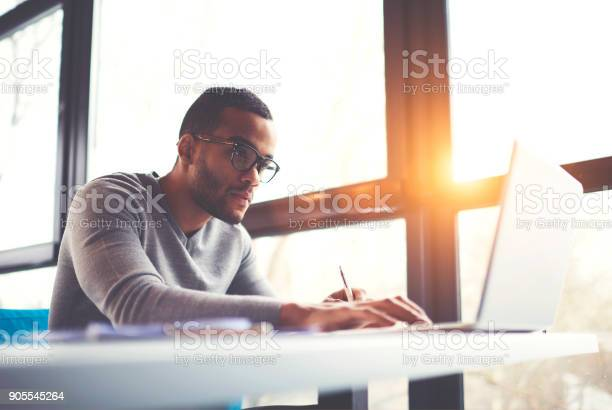 Concentrated dark skinned copywriter in eyewear typing text of publication for web site working on freelance, serious afro american student searching information for homework project in network