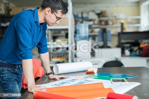 Serious concentrated male designer in blue shirt standing at table and analyzing quality of banner while thinking about paper for printing in printing house