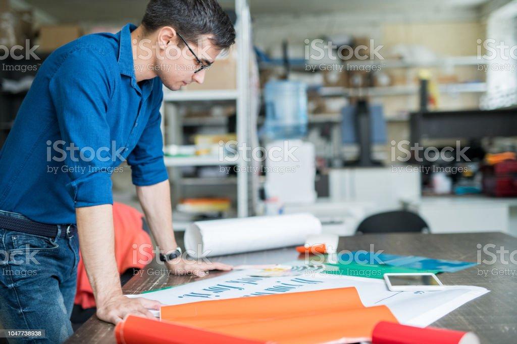 Konzentriertes Designer nachdenken über Papier für den Druck – Foto