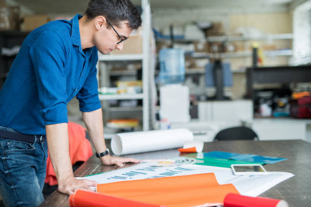 Concentrated designer thinking about paper for printing Serious concentrated male designer in blue shirt standing at table and analyzing quality of banner while thinking about paper for printing in printing house printing plant stock pictures, royalty-free photos & images