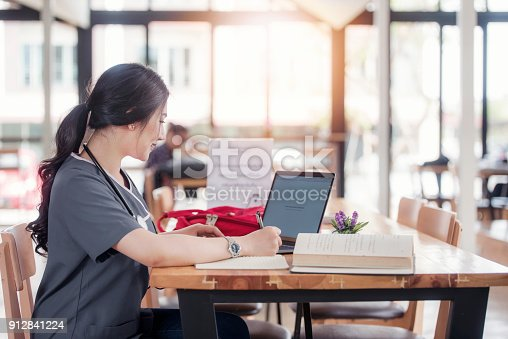 istock Concentrated doctor or nurse working on line with a laptop sitting in a desk in a consultation 912841224