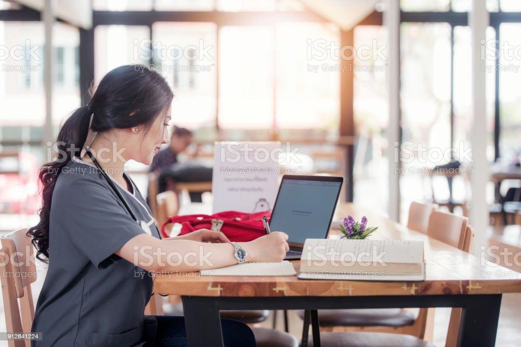 Concentrado de médico ou enfermeiro trabalhando em linha com um laptop sentado em uma mesa em uma consulta - foto de acervo