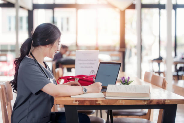 Concentrated doctor or nurse working on line with a laptop sitting in a desk in a consultation stock photo