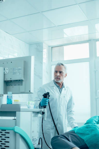 Concentrated doctor ready to conduct endoscopy stock photo stock photo
