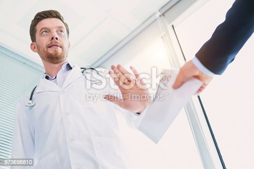 182362845 istock photo Concentrated doctor refusing to take a bribe 973698810