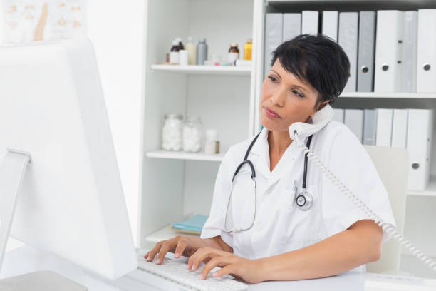 concentrated doctor using computer and telephone - nurse on phone stock photos and pictures
