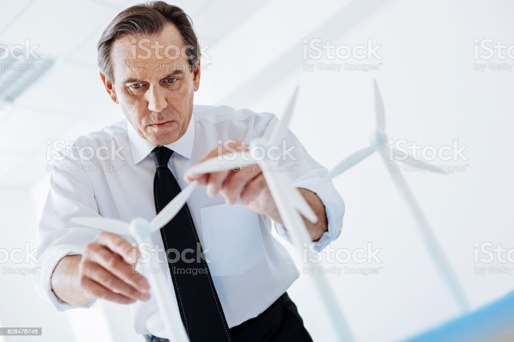 Concentrated engineer adjusting wind turbine sails stock photo