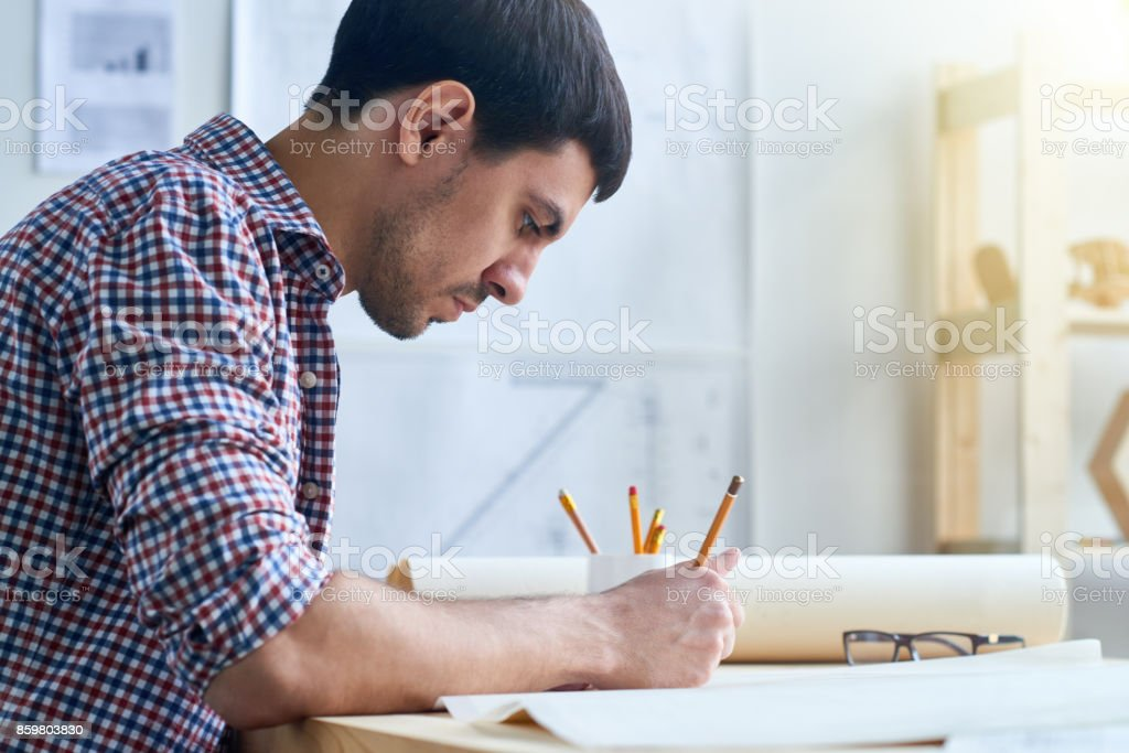 Concentrated engineer working on sketch stock photo