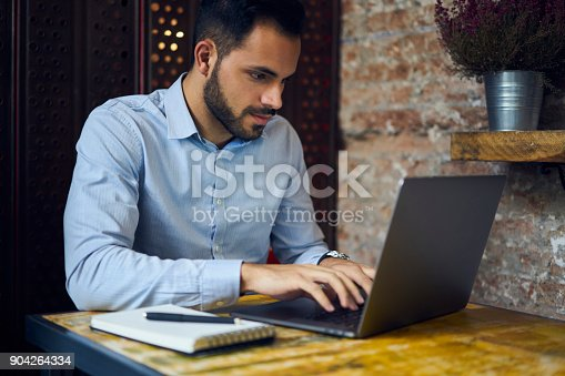 904263506 istock photo Concentrated experienced male entrepreneur communicating through online chat with skilled IT professionals working on creating website for corporation sitting in coworking space using laptop 904264334