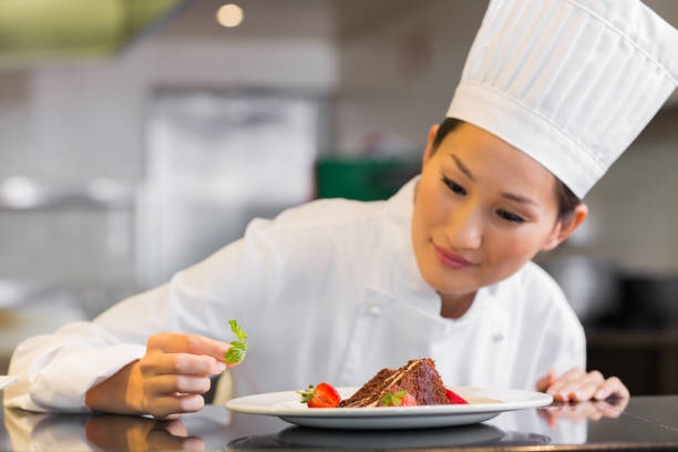 Concentrated female chef garnishing food in kitchen stock photo