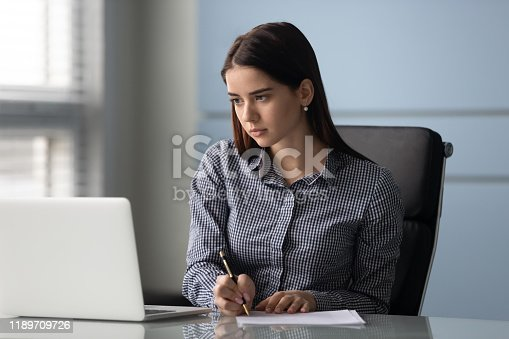 Concentrated young businesswoman write on paper watching business webinar on laptop in office, serious millennial female worker make notes handwrite busy working on computer at workplace