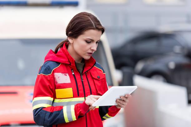 geconcentreerde vrouwelijke paramedicus in uniform met digitale tablet - ambulanceverpleegkundige stockfoto's en -beelden