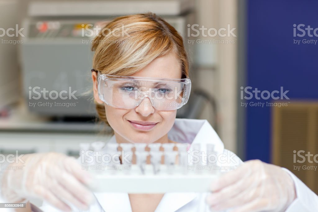 Concentrated female scientist holding samples stock photo