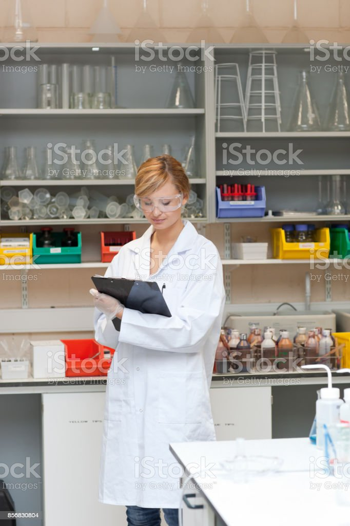 Concentrated female scientist writing on her clipboard stock photo