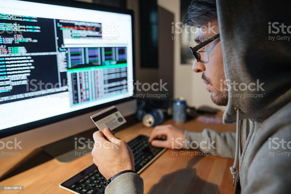Concentrated hacker in glasses stealing money from diferent credit cards stock photo