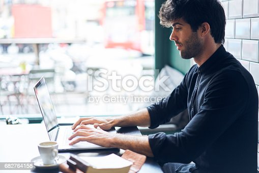 istock Concentrated handsome editor of popular online magazine 682764158