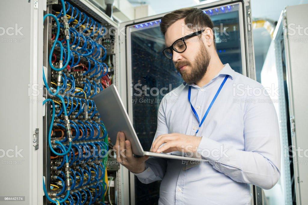 Geconcentreerd knappe technisch specialist in glazen supercomputer via laptop en staande op server rack behuizing in modern opslagruimte beheren - Royalty-free Analyseren Stockfoto