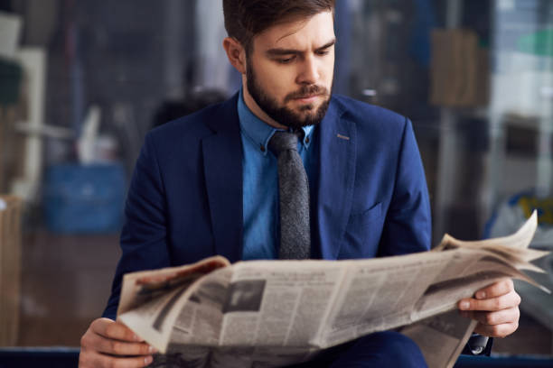 Concentrated handsome young bearded man in blue suit sitting in airport and reading last news to waste time stock photo
