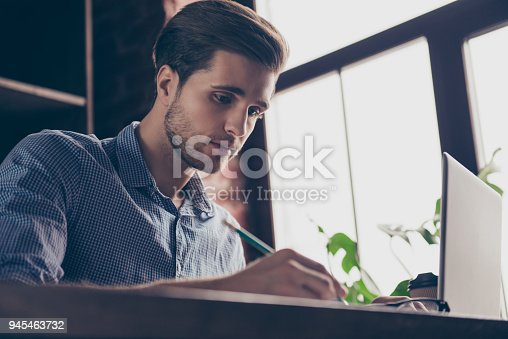 istock Concentrated handsome young man with laptop making notes 945463732