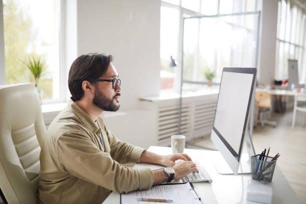 Konzentrierte Hipster asiatische Art Director mit Bart am Tisch sitzen und tippen auf Computer-Tastatur bei der Untersuchung Projektdesign – Foto
