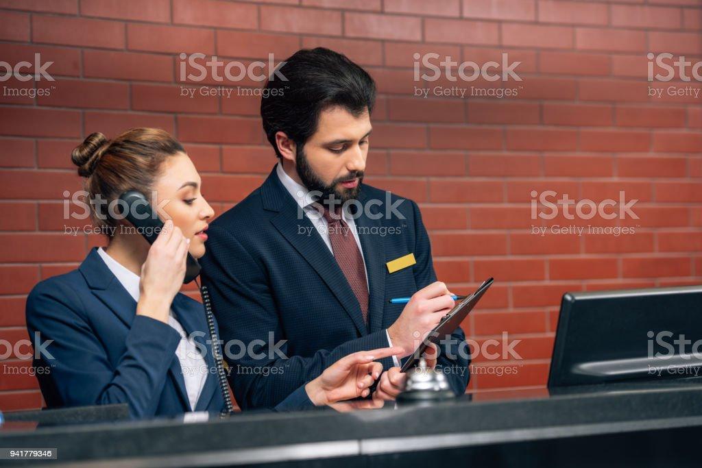 concentré des réceptionnistes d'hôtel réception d'appel du client au lieu de travail - Photo