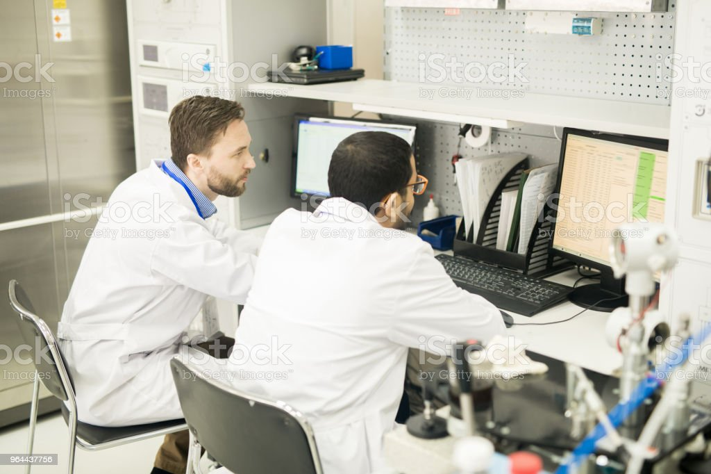Concentrated lab engineers discussing online table on computer - Royalty-free Adult Stock Photo