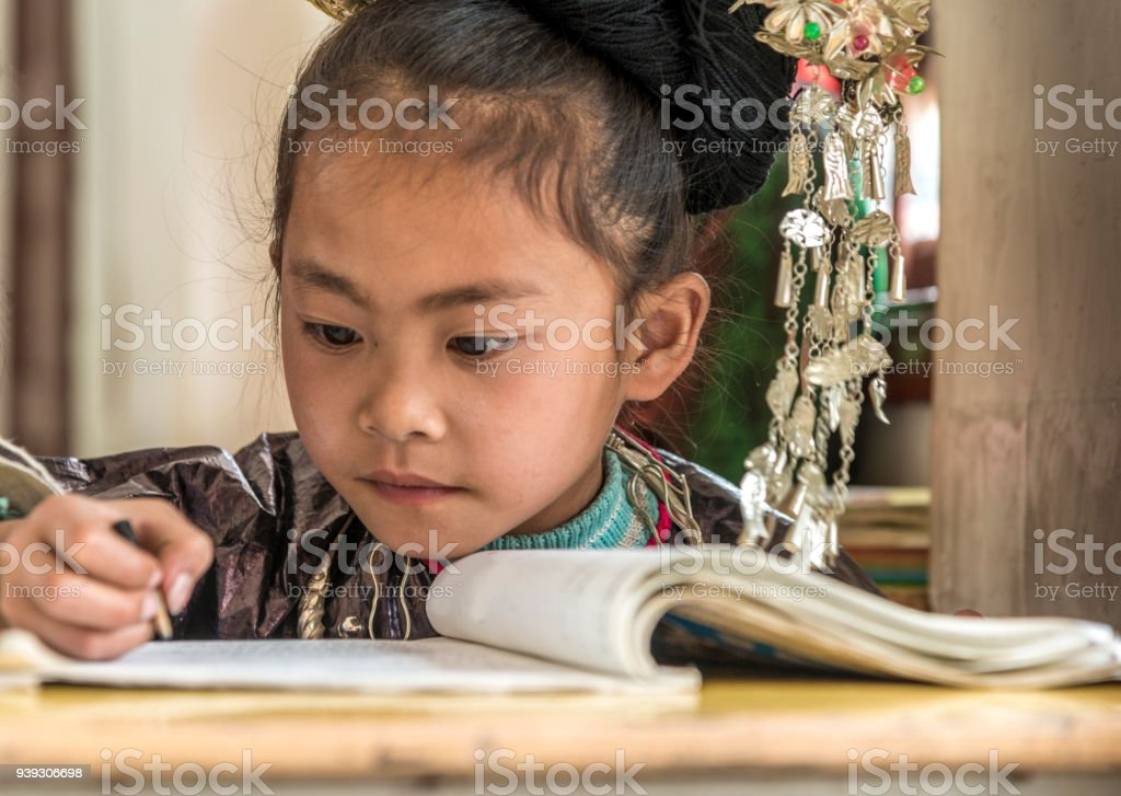 Concentrated Learner School, writing. looking away, selective focus, small Dong Village, Huang Gang.'nChild is dressed in traditional Dong clothing.The Dong is a minority people in China. stock photo