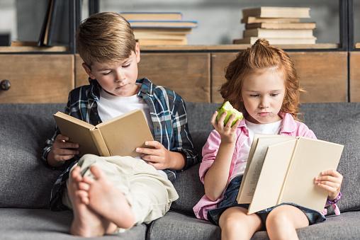 Concentrado Pequeño Hermano Y Hermana Leer Libros En El Sofá En Casa Foto de stock y más banco de imágenes de Alimento - iStock