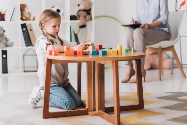 concentrated little child playing with blocks while psychologist sitting blurred on background concentrated little child playing with blocks while psychologist sitting blurred on background autism stock pictures, royalty-free photos & images