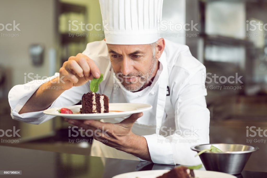 Closeup of a concentrated male pastry chef decorating dessert in the...