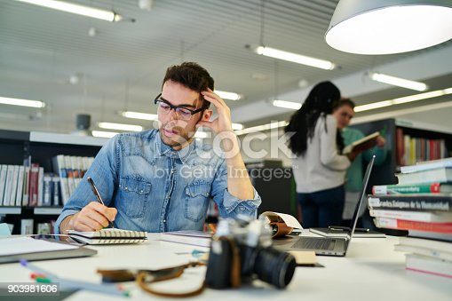 Concentrated male student in eyeglasses thinking about new thesis for writing coursework while making notes in notepad sitting in university library with different books in searching useful literature