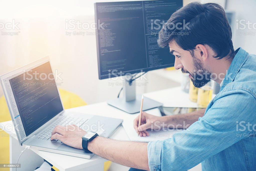 Concentrated man coding on a laptop Note it. Concentrated handsome young man coding on a laptop while noting something and working as a programmer in an office Computer Programmer Stock Photo