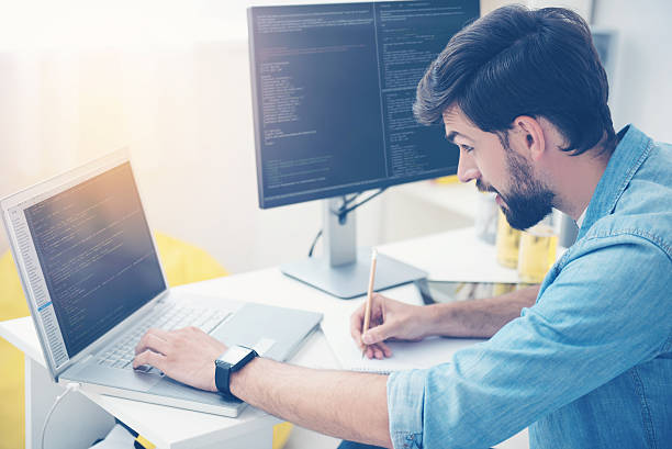 Concentrated man coding on a laptop stock photo