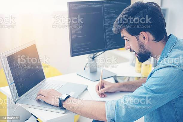 Concentrated Man Coding On A Laptop Stock Photo - Download Image Now