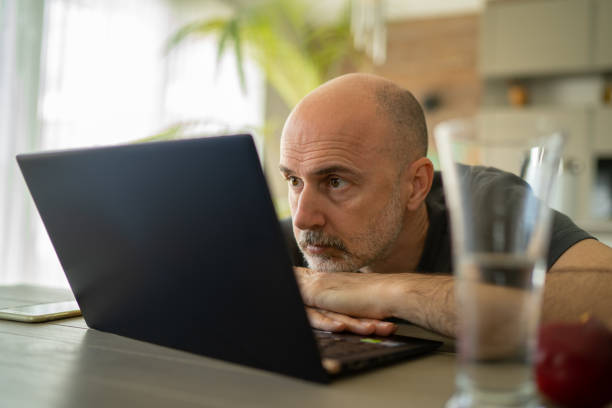 concentrated man looking at laptop working from home during coronavirus quarantine stock photo