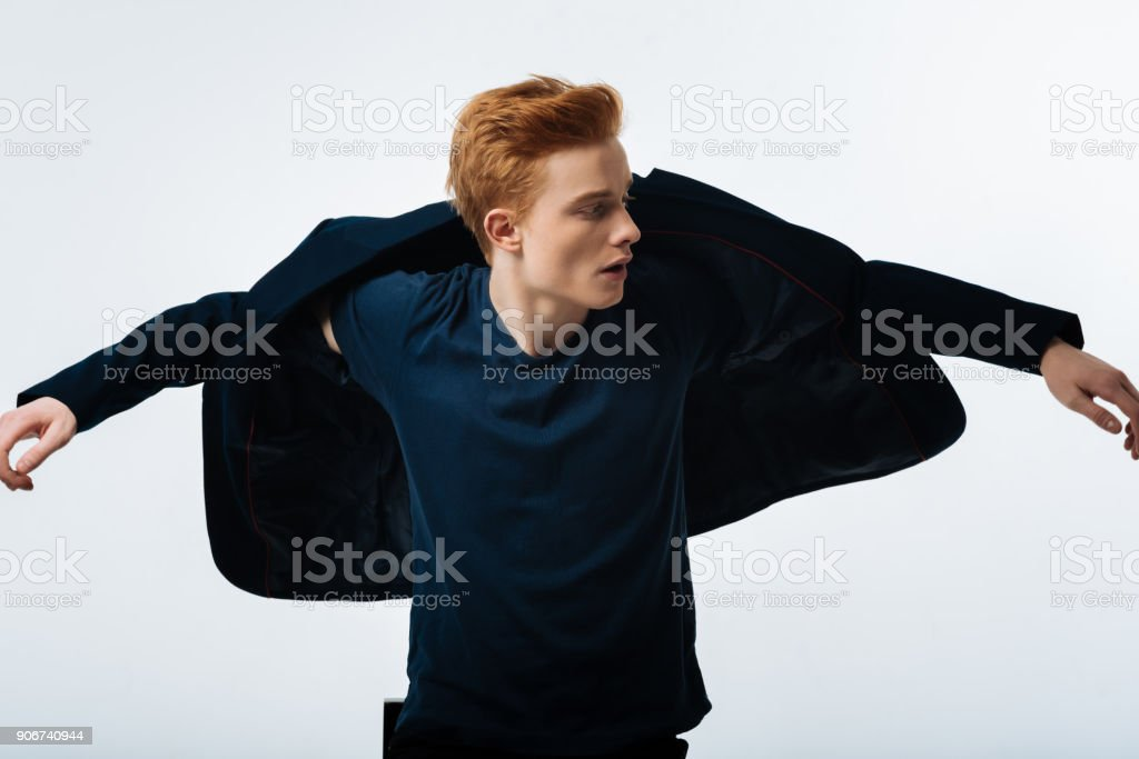 Concentrated man putting his jacket on stock photo