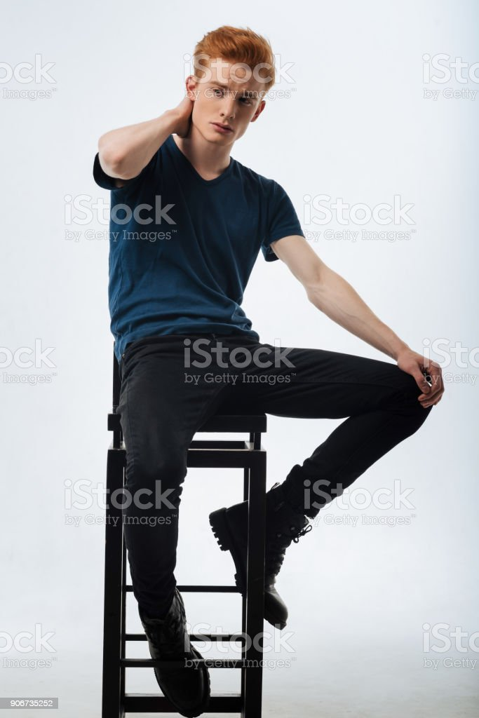 Concentrated man sitting on the chair and thinking stock photo