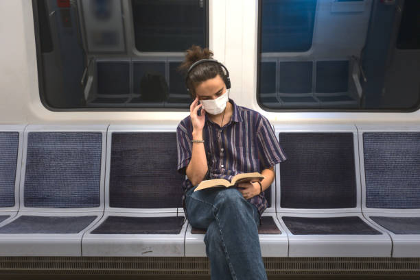 Concentrated masked millennial reading a book and listening to music in subway stock photo