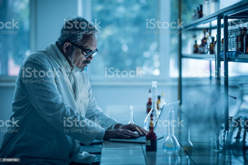 Concentrated Mature Biochemist Working On Laptop In A Laboratory ...