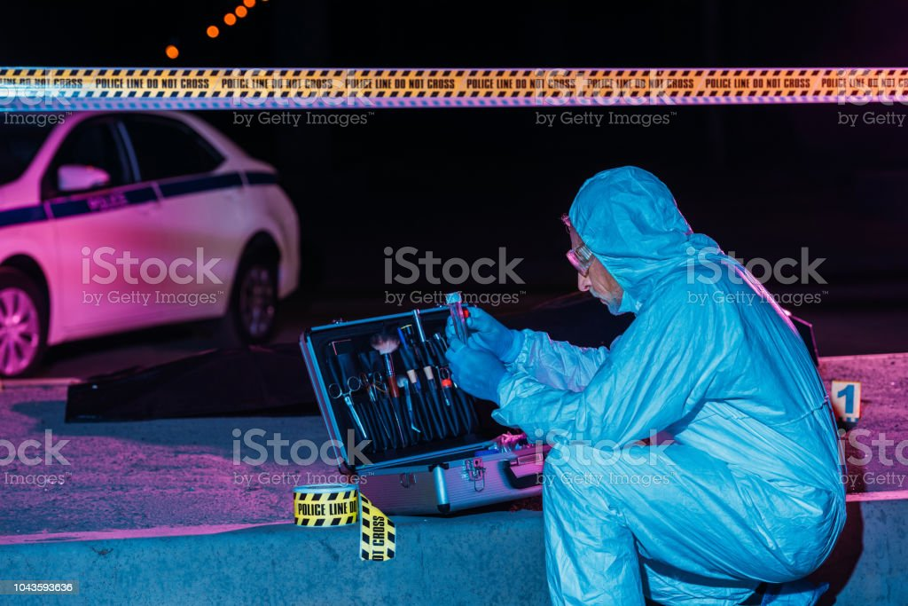concentrated mature criminologist in protective suit and latex gloves collecting evidence at crime scene with corpse stock photo