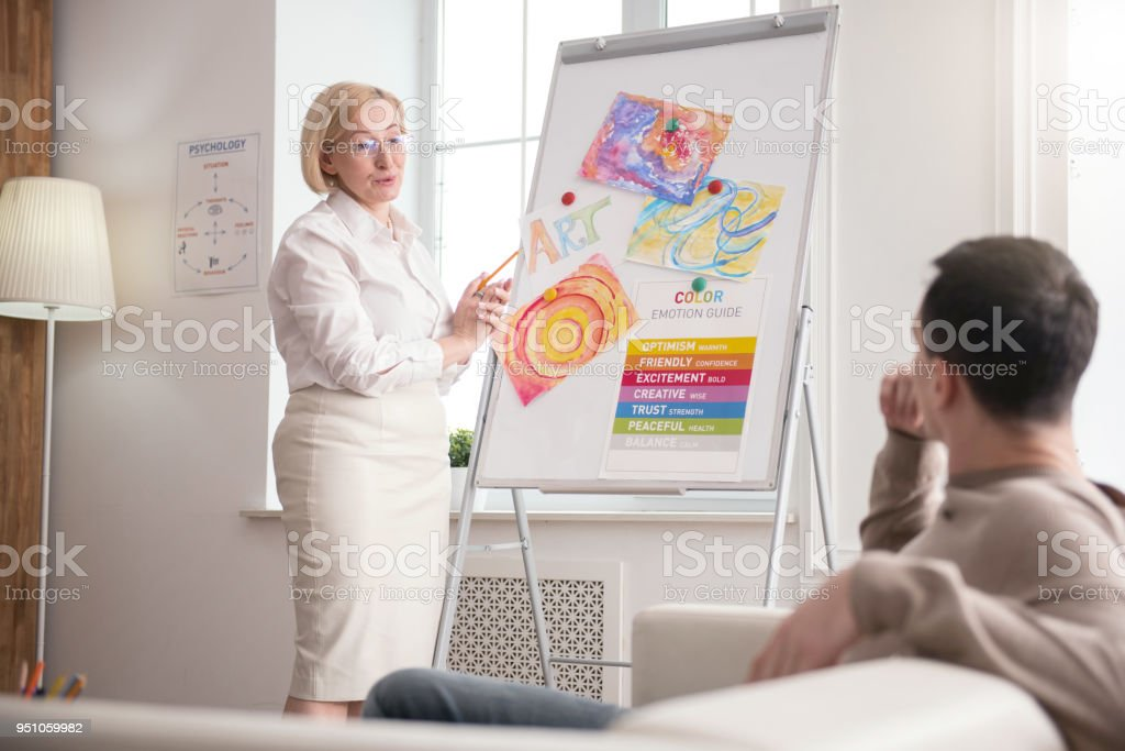 Concentrated mature psychologist enumerating advantages stock photo