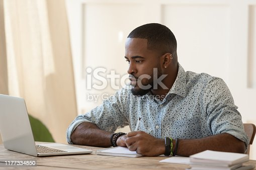 Concentrated millennial african american guy sitting at table, looking at laptop monitor, focused on online university courses study, listening to tutors educational video, writing down notes.