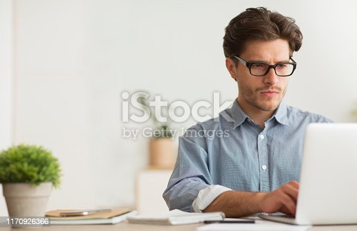 Serious Entrepreneur Working On Laptop Computer At Work. Empty Space For Text