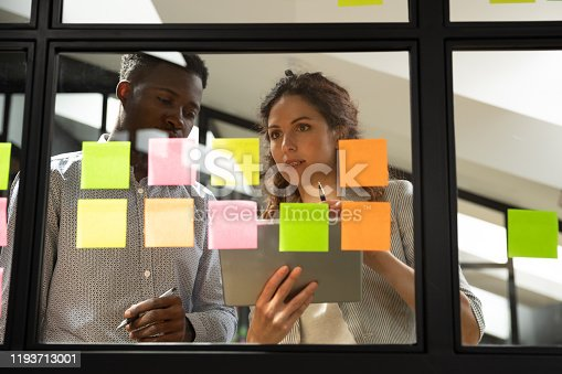 1144568493 istock photo Concentrated mixed race young colleagues standing near glass kanban board. 1193713001