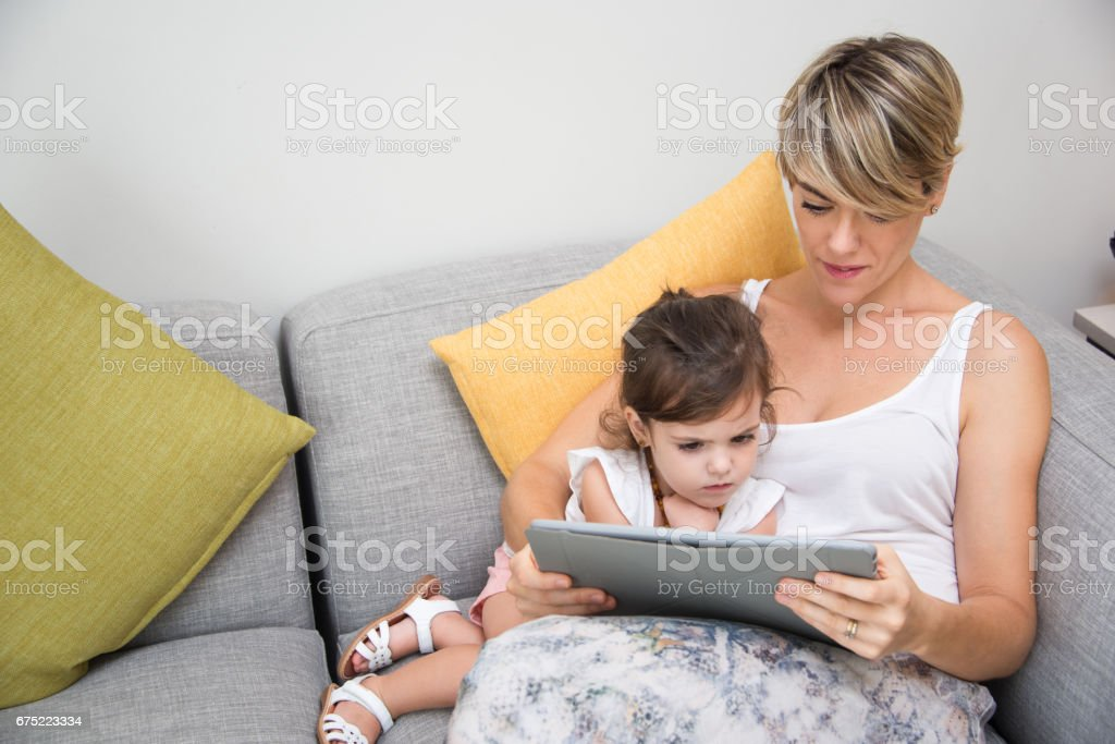 Concentrated mother and daughter using tablet royalty-free stock photo