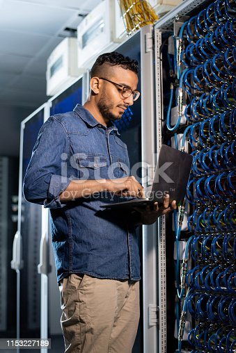 istock Concentrated network engineer examining database server 1153227189