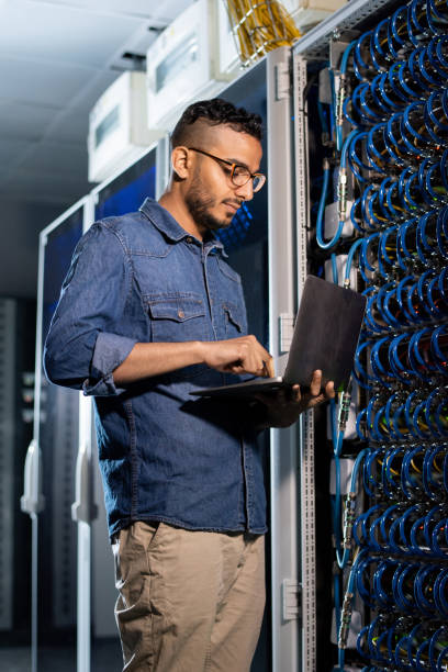 concentrated network engineer examining database server - shironosov stock pictures, royalty-free photos & images