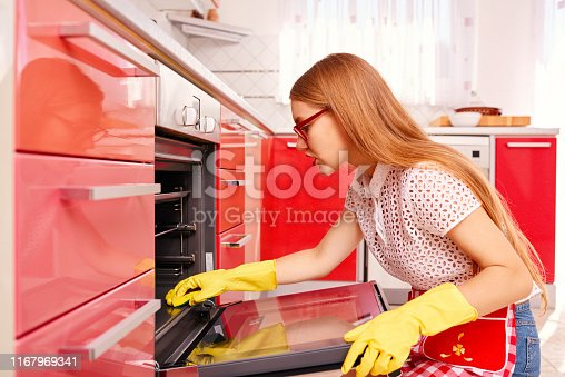 Blonde girl concentrated on cleaning the oven; wearing protective gloves