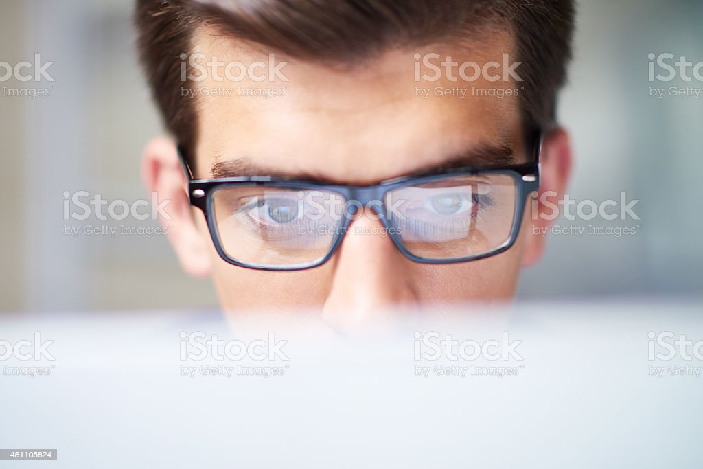 Concentrated on work Intelligent man in eyeglasses working on computer 2015 Stock Photo