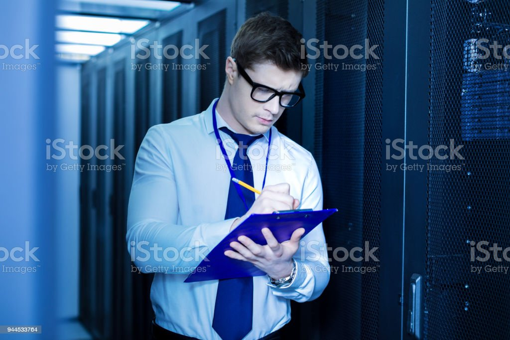 Concentrated operator taking important notes stock photo